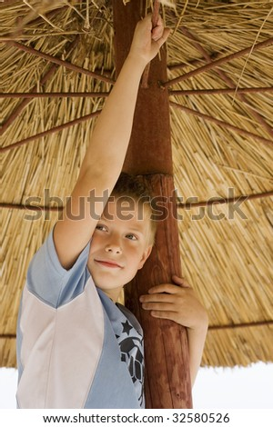 nice young boy playing under a natural beach umbrella