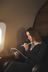 Nice young businesswoman in formal attire, with makeup, looking at screen of tablet with satisfied expression, working remotely while flying on private jet. Business, traveling and technology.