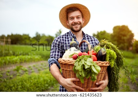 Nice young farmer with freshly picked vegetables in basket #621435623