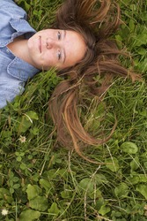 Nice young girl lying on the grass, top view, picture with space for text.