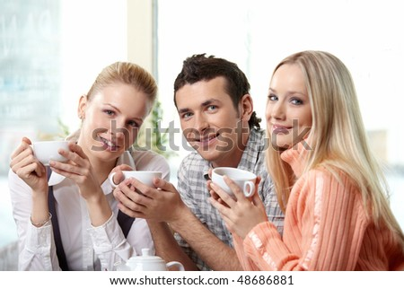 Nice young people drink coffee on a forward background