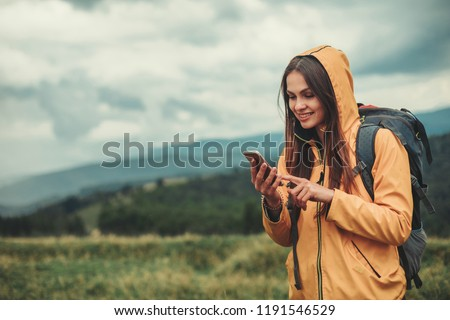 Nice young woman using her mobile phone while enjoying her weekend in the mountains