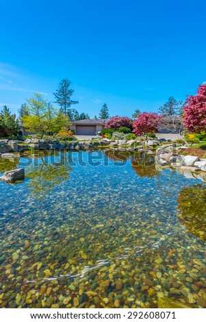 Nicely decorated and designed pond in the great neighborhood of Vancouver, Canada. Landscape design. Vertical.