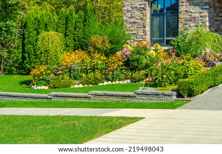 Nicely decorated colorful flowerbed and trimmed bushes at front yard lawn in front of the house and empty pedestrian sidewalk. Landscape design.