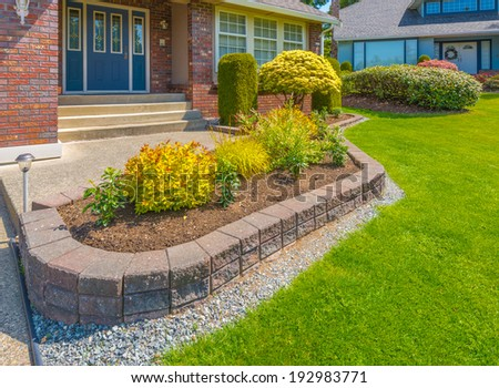 Nicely decorated colorful flowerbed, front yard, lawn with stones and bushes as a decorative elements. Landscape design.