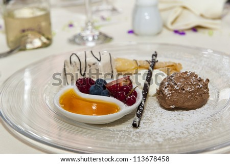 nicely decorated dessert standing on table with sweet creams and fresh fruits