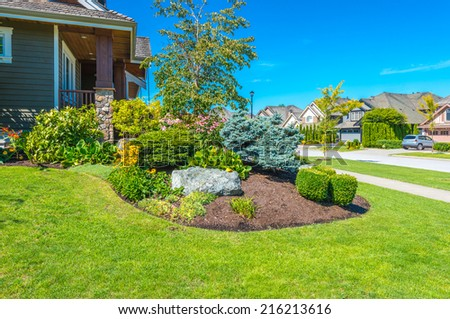 Nicely decorated front yard. Flowers and stones in front of the house. Landscape design.