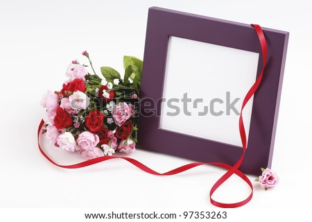 Nicely displayed blank picture frame with fake bouquet of roses and red ribbon