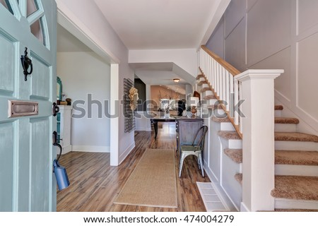 Nicely furnished hallway interior with vintage cabinet and white railings staircase. Northwest, USA #474004279