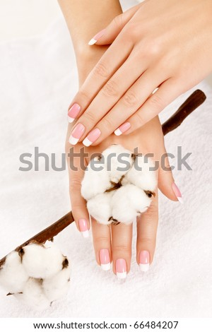 Nicely manicured hands with cotton crop over a towel