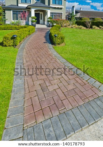 Nicely paved long doorway and trimmed front yard. Entrance to the house.