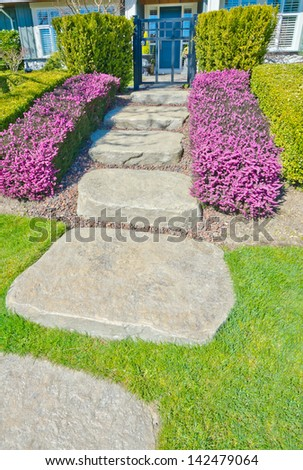 Nicely stoned and paved house doorway, trail with some flowers and trimmed bushes aside steps. Landscape design. House entrance.