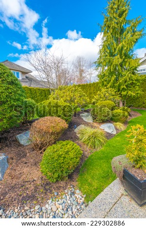 Nicely trimmed and landscaped front, back yard. Flowers and stones in front of the house, front yard. Landscape design. Vertical.
