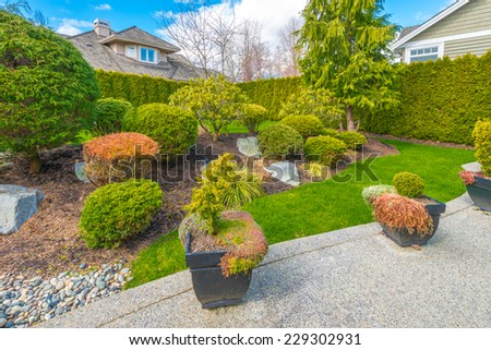 Nicely trimmed and landscaped front, back yard. Flowers and stones in front of the house, front yard. Landscape design.