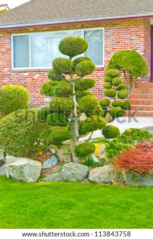 Nicely trimmed and landscaped front yard, entrance to the house. Landscape design.