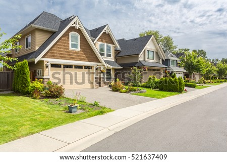 Shutterstock Nicely trimmed and manicured garden in front of a luxury house on a sunny summer day. Street of houses in the suburbs of Canada.