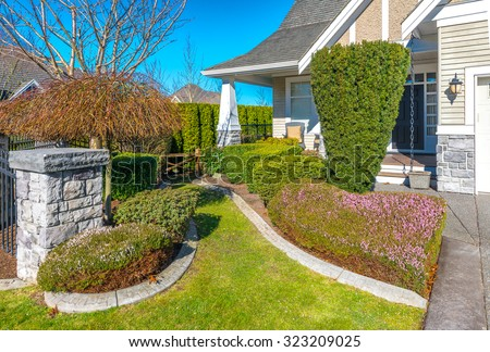 Nicely trimmed bushes, flowers and stones in front of the house, front yard. Landscape design.