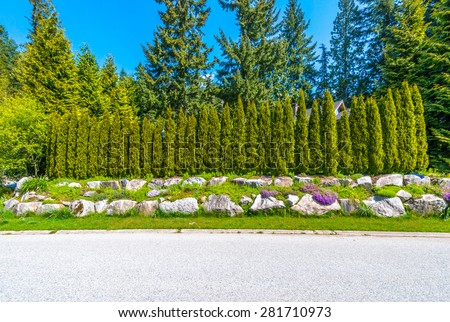 Nicely trimmed bushes, green fence  in front of the house, front yard. Landscape design.
