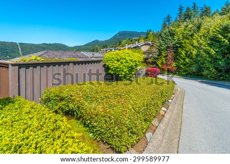 Nicely trimmed bushes  in front of the house, front yard on the empty street. Landscape design.