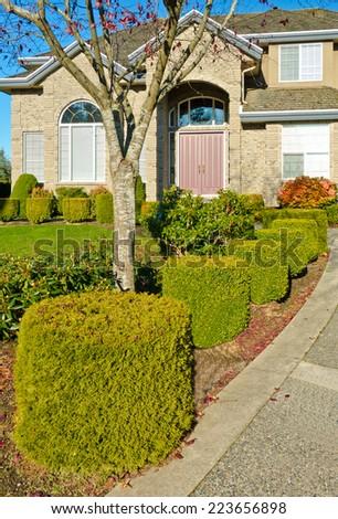 Nicely trimmed bushes in front the house.  Landscape design.