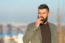 Nicotine abuse. Cigarette smoker. Bearded man smoke nicotine cigarette outdoor. Addiction to nicotine. Smoking habit comes from nicotine dependence Bad habit.