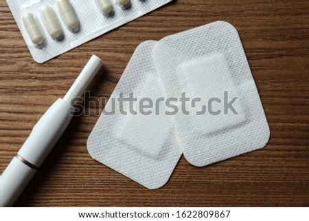 Nicotine patches, pills and electronic cigarette on wooden table, flat lay Stock photo ©