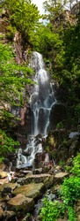 Nideck waterfall near the ruins of the medieval castle in Alsace, France. Vertical panorama.
