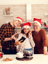 Niece taking selfie with granddparents celebrating christmas in decorated kitchen. Happy cheerful multi generation family using phone to take photo wearing santa hat doing hand gesture with xmastree
