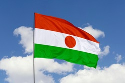 Niger flag isolated on the blue sky with clipping path. close up waving flag of Niger. flag symbols of Niger.