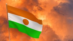 Niger flag on pole. Dramatic background. National flag of Niger