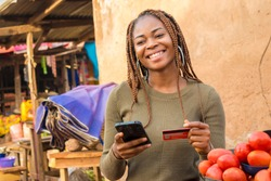 nigerian lady selling in a local nigerian market using her mobile phone and credit card to do a transaction online smiling