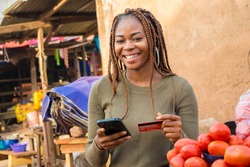 nigerian woman selling in a local nigerian market using her mobile phone and credit card to do a transaction online smiling