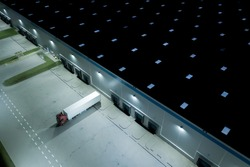 Night Aerial top view of truck and cargo trailer unloading in logostics center.