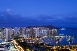 Night aerial view of Honolulu with Ilikai Marina in the foreground and a distant view of the Diamond Head