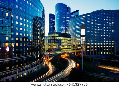 Night architecture - skyscrapers with glass facade. Modern buildings in Paris business district. Evening dynamic traffic on a street. Concept of economics, finances.  Copy space for text. Toned