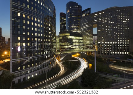 Night architecture - skyscrapers with glass facade. Modern buildings in Paris business district. Evening dynamic traffic on a street. Concept of economics, financial.  Copy space for text. Toned #552321382