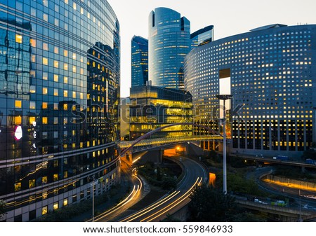 Night architecture - skyscrapers with glass facade. Modern buildings in Paris business district. Evening dynamic traffic on a street. Economy and finances concept. Copy space for text. Toned #559846933