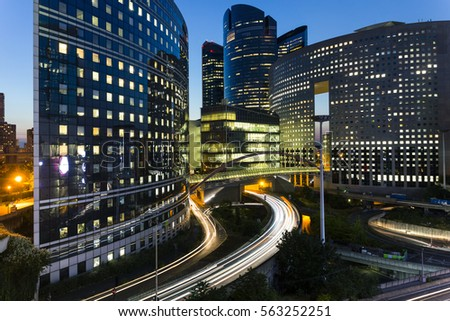 Night architecture - skyscrapers with glass facade. Modern buildings in Paris business district. Evening dynamic traffic on a street. Concept of economics, financial.  Copy space for text. Toned #563252251