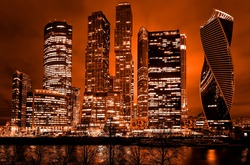 Night architecture - skyscrapers with glass facade. Modern buildings in red tone.