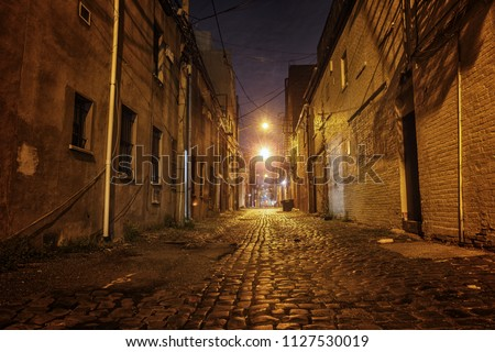 night back street, looks dangerous and deserted with nobody and mystery, bricks road.