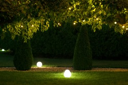 night backyard with mown lawn and trees festive decorated with garlands with light bulbs in the leaves of trees and ground ball lanterns on celebrate of party holiday, nobody.