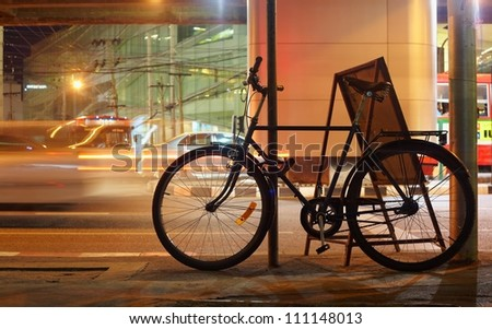 Night bicycle silhouette against city car light motion