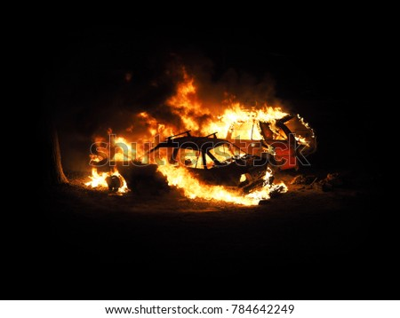 Night. Burning cars, unrest, anti-government. Consequences of the collision, crime. Car on fire isolated on black background