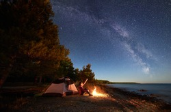 Night camping at sea shore. Female backpacker sitting in front of tourist tent at campfire near forest, pointing to sky full of stars and Milky way, enjoying beautiful view of clear blue water