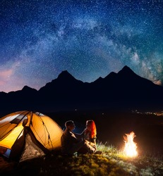 Night camping. Happy couple hikers sitting face to face in front tent near campfire under shines starry sky. On the background silhouettes of the high mountains and luminous village in the valley