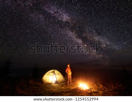 Night camping in mountains. Tourist woman standing near illuminated tent and brightly burning campfire. Female hiker enjoying dark sky with lot of bright sparkling stars and Milky way on background #1254552994