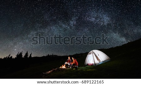 Night camping in the mountains. Couple tourists have a rest at a campfire near illuminated tent under amazing night sky full of stars and milky way. Low light. Picture aspect ratio 16:9
