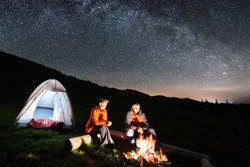 Night camping in the mountains. Man and woman tourists have a rest at a campfire near illuminated tent under incredible night sky full of stars and milky way. Low light