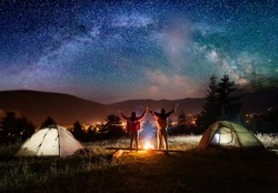 Night camping. Pair hikers stands and holding hands lifting up from enjoying the beautiful night sky with stars and Milky way