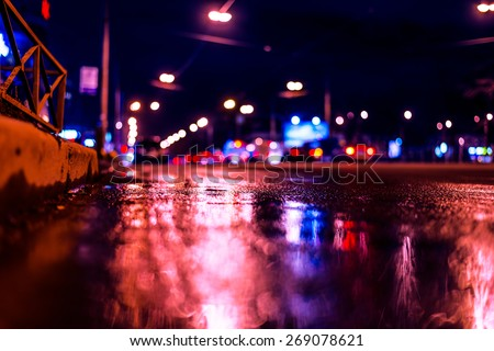 Night city after rain, night view of the busy highway from the curb at the asphalt level. Image in the blue-purple toning